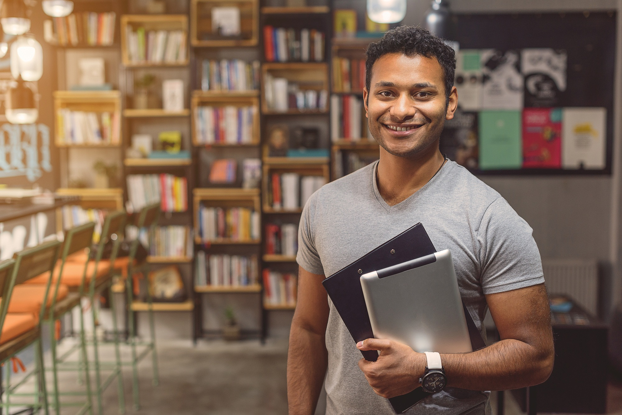 African man standing in campus library
