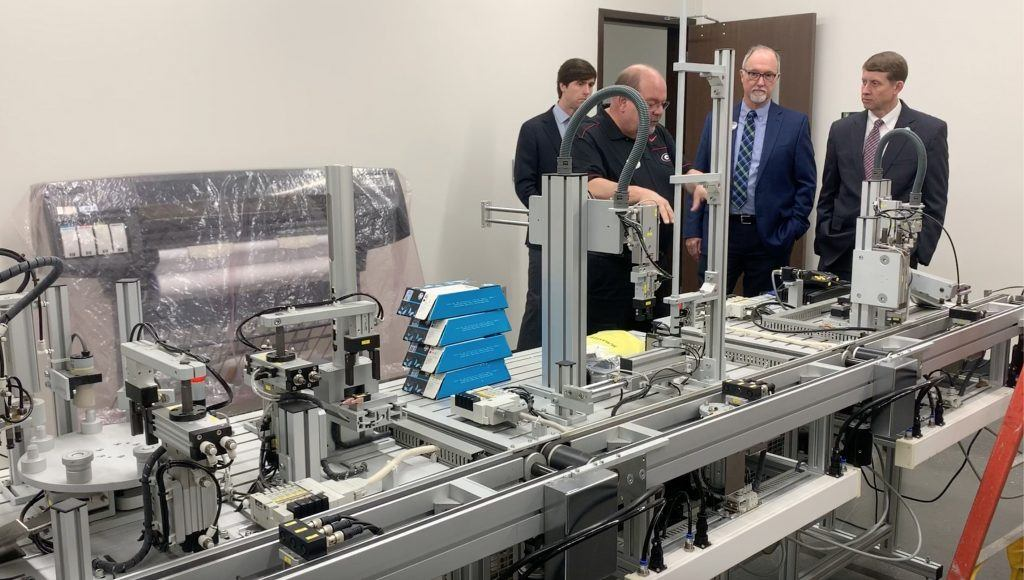 Joey Watkins explains the importance of advanced PLC manufacturing line training to Commissoner Dozier as TCSG Asst. Commissioner Neil Bitting and Dr. Perren look on.