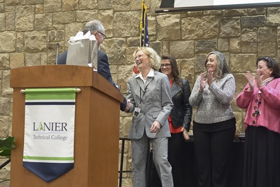 Photo of Annette Baker learning of award and being congratulated by Dr. Ray Perren, Lanier Technical College President.