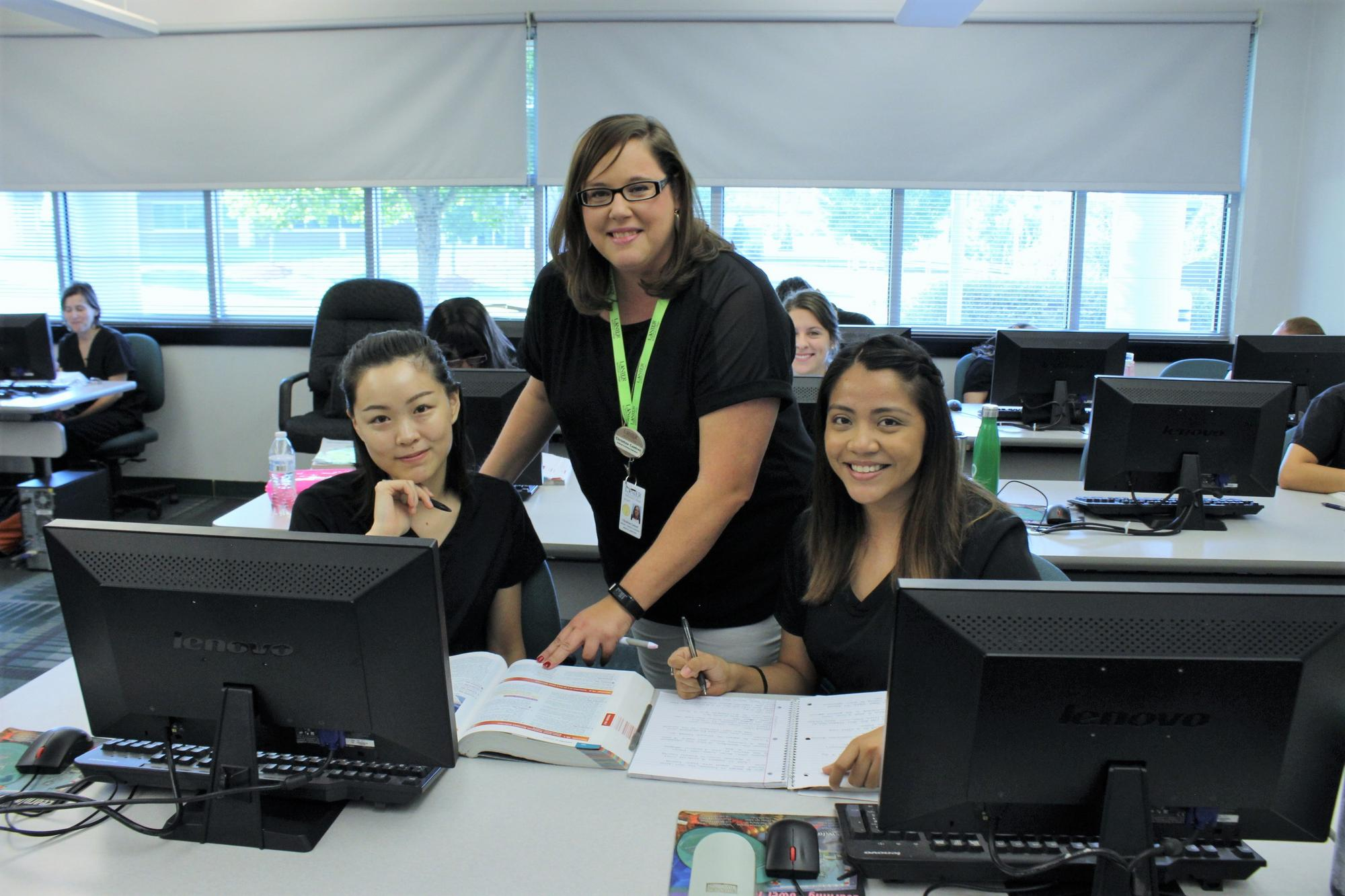 Instructor assisting two female students in computer lab